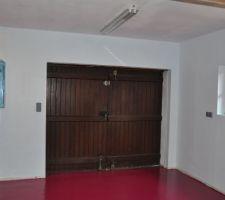 Le garage avec sa porte en bois