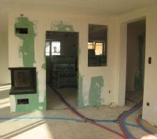 vu de la salle a manger vers la cuisine en face le salon a gauche et le couloir a droite