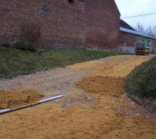 etalement du sable pour corriger les niveaux et compactage avec le rouleau compacteur en photo en haut de la pente