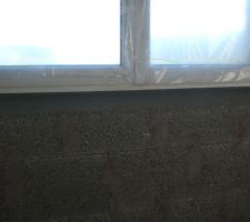 Soubassement béton sous fenêtre, tiré à l'oblique, problématique pour la projection d'un enduit projeté