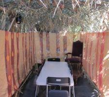 les branches de palmier sont placees sur le toit et les murs de la structure