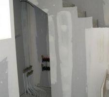 placard sous escalier qui acceuille les tuyaux pour les reglages des tuyaux pour le plancher chauffant