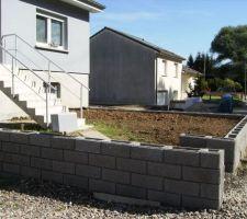 Mise en place du muret devant la maison, ajout de terre pour arriver au niveau du muret. En attente du niveau fini par rapport au trottoir pour faire le pavage.