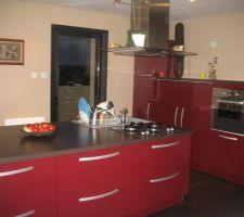 cuisine americaine rouge laquee avec plan de travail wenge de 2m 40 par 1m20 et poignees large en alu hotte centrale