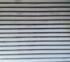 Vue détaillée du portail de garage : ce sont des lames ajourées pour rappeler visuellement nos brise soleil