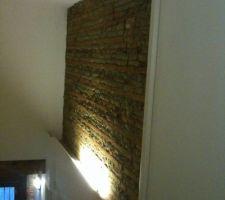 Vue dans de l'entrée avec passage des alimentations et tuyauteries du split du salon le long du mur en briques et galets