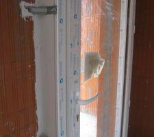 Isolation (côté intérieur) de la porte balcon de la cuisine avec du silicone. On voit aussi des pattes de fixation au mur
