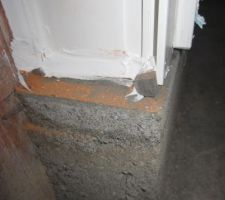 Zoom de la photo précédente. Au sol à droite on voit le petit morceau de mousse qui sort de dessous la fermeture. L'étanchéité à l'air est assurée par le poids de la fermeture qui compresse la mousse. Du silicone est posé au sol entre la mousse et le mur pour compléter l'étanchéité