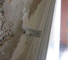 Zoom sur la fenêtre trapézoïdale précédente. On voit une fixation au mur et le silicone