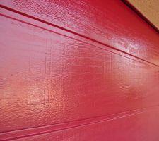 Vue rapprochée de la partie haute du portail ou la peinture a moins vieilli en raison de l'avancée de toiture qui le protège un peu