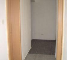 couloir allant du salon salle a manger vers l entree on voit l entree qui est differencier par le carrelage gris fonce et la frise au sol qui separe