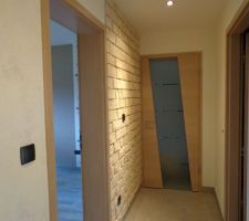 L'entrée du couloir nuit avec un mur en pierres de parement et le papier blanc.