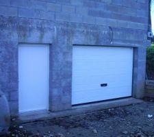 La porte de garage sectionnelle motorisée et la porte de service,  en pvc Blanc.