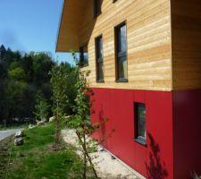 Bardage en Mélèze non traité à l'étage  Bardage en Fundermax au rez-de-jardin (mélange de fibre de bois naturelles 65% avec 35% de résines synthétiques).  Couleurs: - Rouge Rubinus Réf.3003 - Ivoire Clair Réf.0073