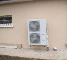 L'unité extérieure est de marque Viessmann, série Vitocal 200-S de 14,6 KW, à puissance modulante, avec coefficient de performance COP de 4,29. L'unité extérieure qui regroupe évaporateur, compresseur, détendeur et ventilateur (d'une remarquable tenue aux intempéries d'après la publicité) est implantée, grâce à des dimensions réduites, directement sur la façade du garage. Ecologique, elle n'exploite que la chaleur contenue dans l'air extérieur. Le bruit de fonctionnement est minimum grâce à la marche modulée qui réduit la nécessité permanente d'activer et de désactiver l'appareil. Le ventilateur avec réglage de la vitesse et le compresseur se révèlent beaucoup plus silencieux qu'un fonctionnement permanent à la puissance maximale. Grâce à sa marche modulée, la pompe à chaleur adapte avec précision la puissance du compresseur aux besoins et garantit la température souhaitée. Elle est aussi économique en fonctionnement à charge partielle grâce à l'utilisation d'un inverseur. Le dégivrage performant est assuré par inversion de cycle. Température de départ maximale : jusqu'à 55° à une température extérieure de -15°. La Vitocal 200-S devrait s'avérer assez économique en charge partielle (technologie DC-Inverter). En effet, la puissance de son compresseur s'ajuste automatiquement aux besoins de chauffage et maintient ainsi la température désirée en consommant un minimum d'énergie. Le fonctionnement modulant de la Vitocal 200-S réduit ainsi la fréquence des cycles de fonctionnement et devrait permettre une longévité importante.