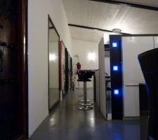 A gauche la porte du bureau,puis la coursive autour de l'escalier et le meuble a 5 colonnes