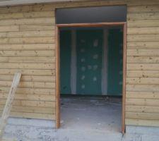 Le menuisier continue avec l'installation du cadre de la porte d'entrée et des fenêtres