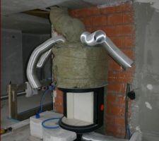 La cheminée en cours de finition avec les prises d'air frais en bas et les distribution d'air chaud en haut. Une des quarte traversera le mur en brique pour chauffer la sdb parents derrière.