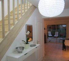 L'entrée, l'escalier vernis, la porte du sous-sol et la vue qui se prolonge vers le séjour et le jardin.