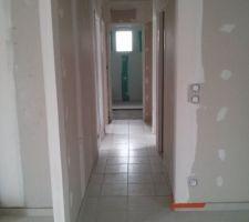 Vue du couloir, la salle de bain au fond carrelage non terminé