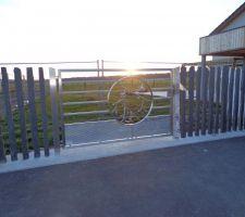 Voici le portail inox pour accéder au jardin depuis l'avant de la maison avec le mur en piquet d'ardoise