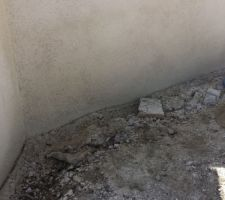 En plus de voir les joints des parpaings, il se trouve que l'ouvrier n'a vraisemblablement pas respecter le dosage ciment/sable/colorant... L'aspect noir du mur vient du fait que les tout petits gravillons (limite gros grains de sable) ressortent... A moins qu'il n'est trop passé l'éponge au point de virer le ciment?